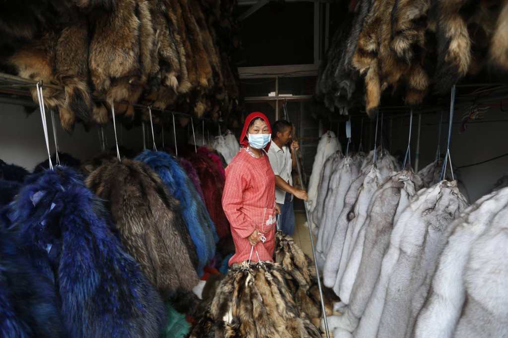 A worker hangs bundles of mink fur inside a store at a fur market in Chongfu township